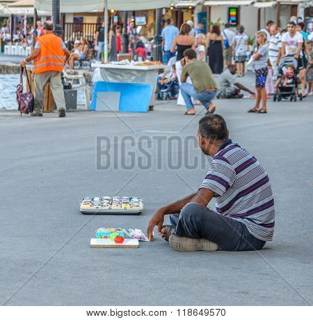 CHANIA, CRETE, GREECE - AUGUST 18, 2013: Man sits on the road and sells souvenirs  at Old Venetian port in Chania town. Many tourists visit Chania every year