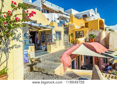 raditional Santorini's buildings with Souvenir shops and cafes with people at Oia town