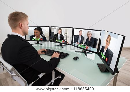 Businessman Video Conferencing On Desk