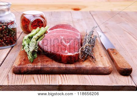 prime fillet meat : dry raw beef on cutting board with asparagus , thyme bundle , color peppercorn mix and red paprika powder mixed with dry spices over wooden table ready to cooking