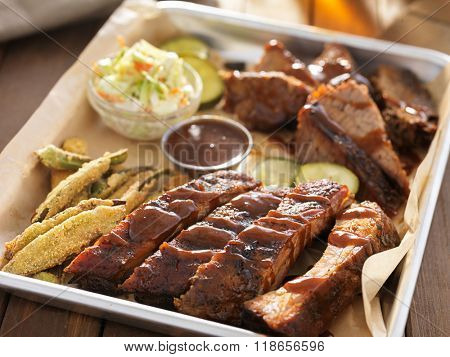 smoked beef brisket with barbecued ribs in platter and fixings