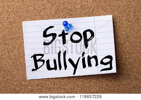 Stop Bullying - Teared Note Paper Pinned On Bulletin Board