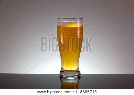 Glass Of Beer With Foam On Gray Background