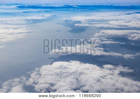 Blue sky with clouds, over landmass and sea background, aerial photography