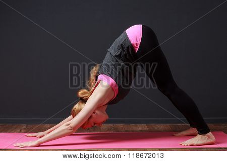 Young Blonde Woman Staying In Downward Dog Pose