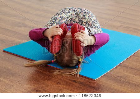 Little Girl Is Doing Stretching Workout On A Mat.