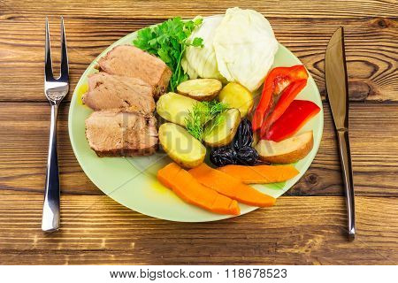 Healthy Food, Sliced Pork Meat With Stewed Various Vegetables In Plate, Knife And Fork On Wooden Bac