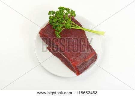 chunk of raw beef meat and fresh parsley on white plate