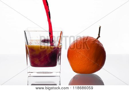 Blackcurrant Juice Pouring Into Glass With Orange Juice