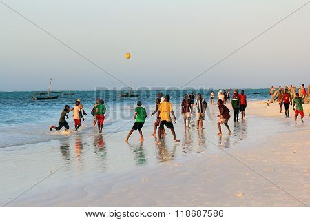 A Game Of Football On The Beach At Sunset
