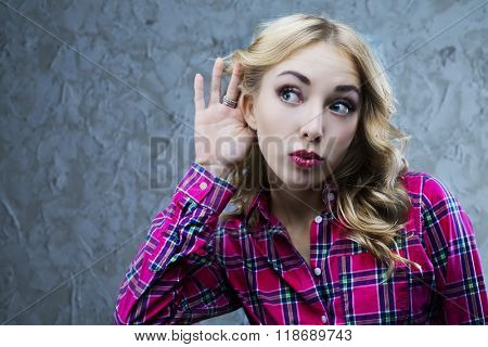 interested young blond woman listening to something, studio shot