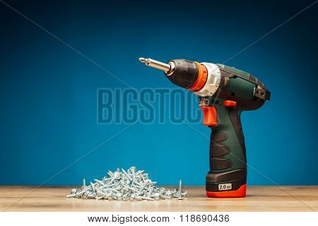 cordless screwdriver and fasteners screws on blue background