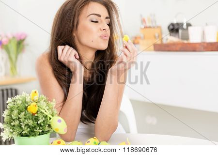 smiling female kissing a little baby easter chicken