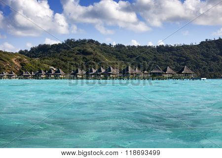 Typical Polynesian landscape - island with palm trees and small houses on water in the ocean and mou