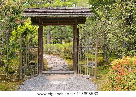 Simple looking wooden gate with roof inside the garden
