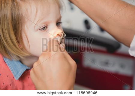 Doctor ENT checking ear with otoscope to girl patient