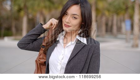 Gorgeous young woman putting purse over shoulder