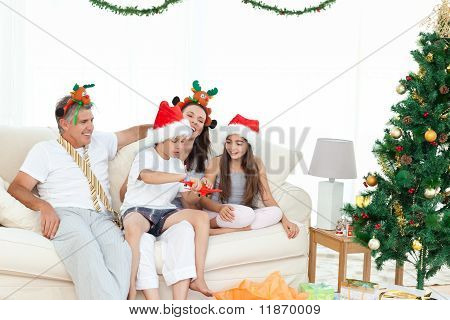 Family During Christmas Day Looking At Their Presents