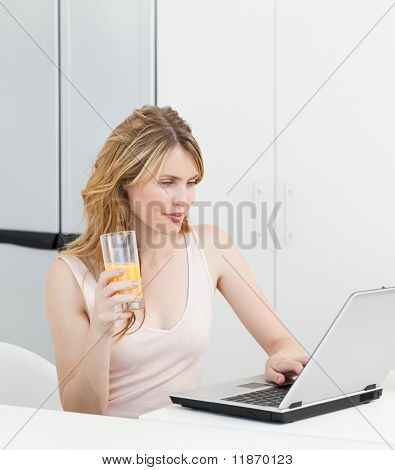 Woman Drinking While She Is Looking At Her Laptop