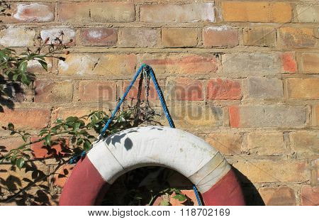 Life Buoy Preserver Attached To A Red Brick Wall With Plenty Of Copy Space