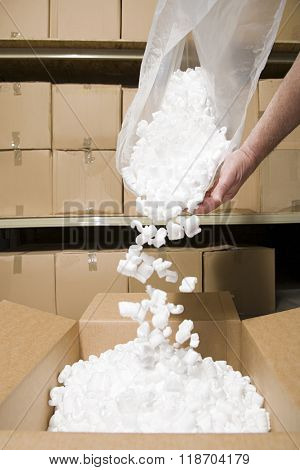 Person putting packing peanuts in box