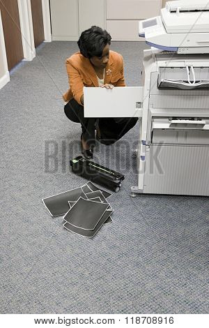 Office worker looking at photocopier