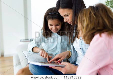 Beautiful Mother With Her Daughters Reading A Book At Home.