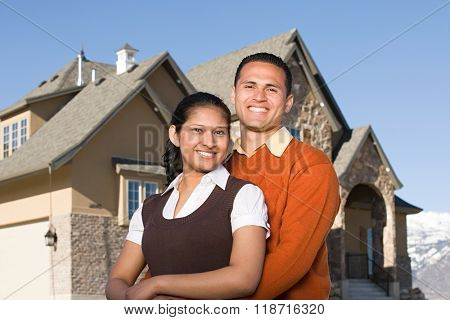Portrait of a couple outside of a house