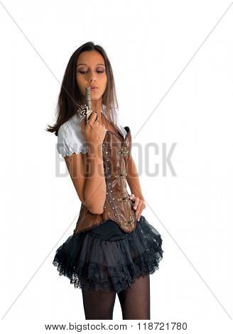 Three Quarter Length Portrait of Young Brunette Woman Wearing Old Fashioned Western Costume with Tutu and Corset Blowing on End of Antique Pistol in Studio with White Background and Copy Space