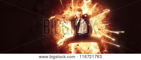 Ambitious motivated businessman leaping through fire with his arms outstretched in a dramatic conceptual portrait of energy and power, over black in banner format