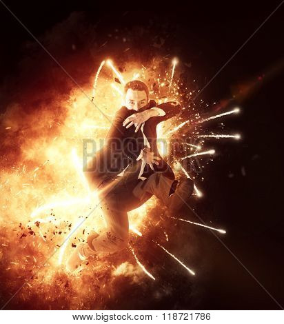 Wide view of leaping businessman in suit and tie surrounded by fiery explosion and flying sparks posed as if throwing something