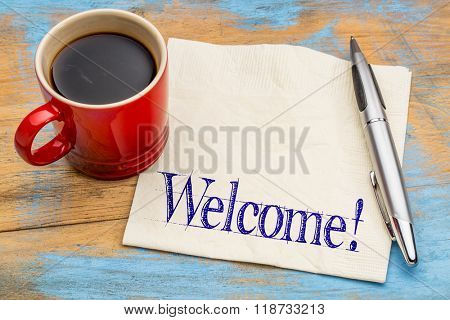 Welcome informal sign - handwriting on a napkin with a cup of coffee