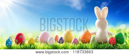 Bunny With Decorated Eggs On Sunny Meadow - Spring And Easter Background
