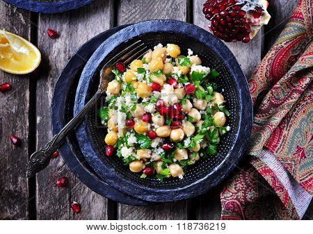 chickpea salad with couscous, parsley, olive oil with pomegranate