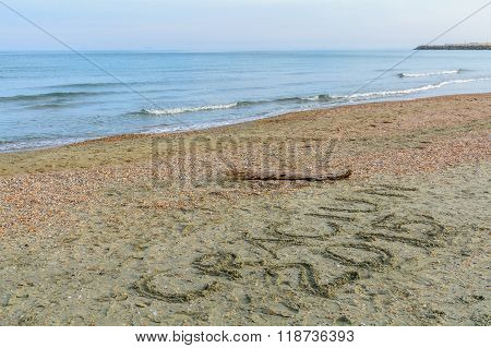 Seashore, Sand And Water With Christmas Message Written. Sea Water And Sand With Shells With