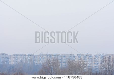 Frozen Dry Trees In Winter And City Panoramic View. Winter Picture With Brown Dry Trees Peaks, City