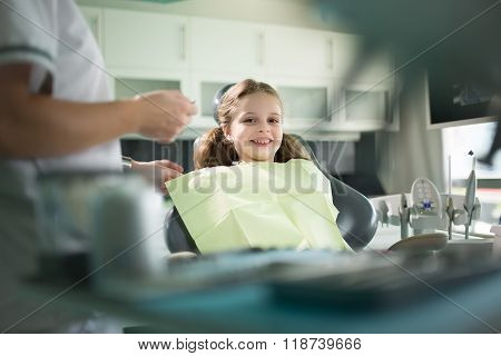 Little girl is having her teeth examined by dentist.Little girl sitting and smiling