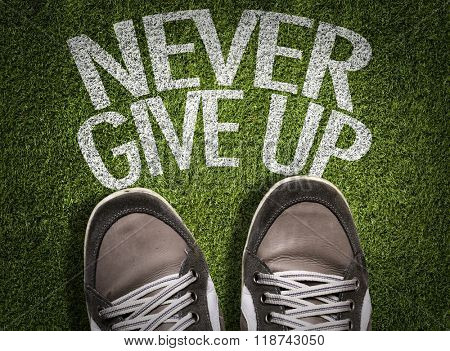 Top View of Sneakers on the grass with the text: Never Give Up