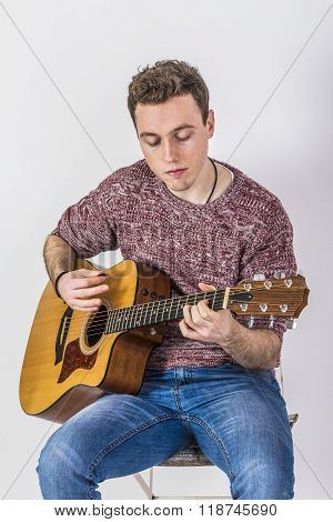 Teenage Guitar Player Sits On A Chair And Plays Western Guitar