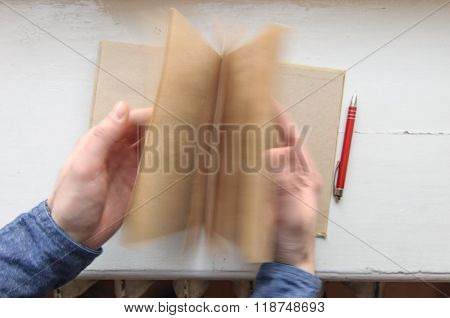 Person holding notebook and flipping pages