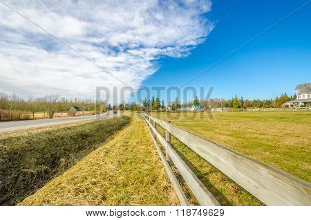 Countryside road with a fence horses hay and cars against blue cloudy sky
