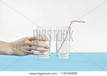 Glass of pure water against sugar, diabetes disease, sweet addiction, hand take a glass