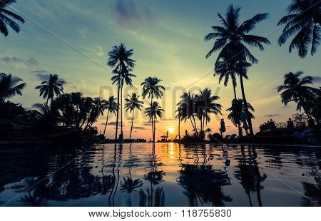 Beautiful sunset on a tropical beach with palm trees reflection in the water.