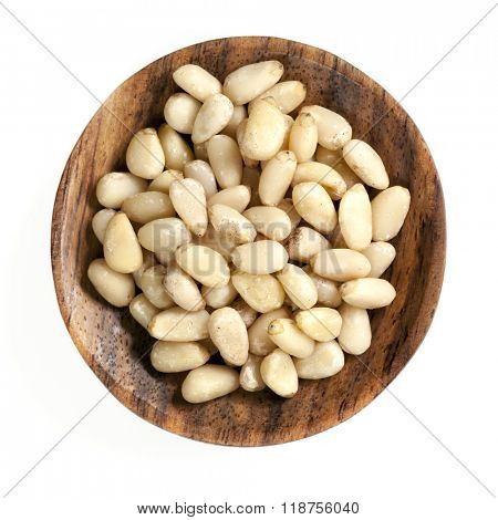 Pine nuts in wooden dish, isolated on white.