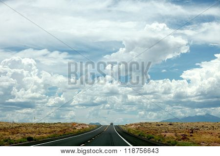 A desolate highway in western Utah winds through the desert under a dramatic sky.