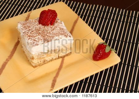 A Piece Of Tiramisu Dusted With Cocoa On A Yellow Plate With Two