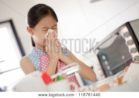 Girl is blowing her nose, allergic to flour
