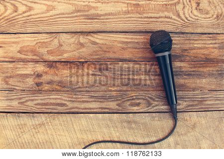 Microphone on wooden background. Toned image.