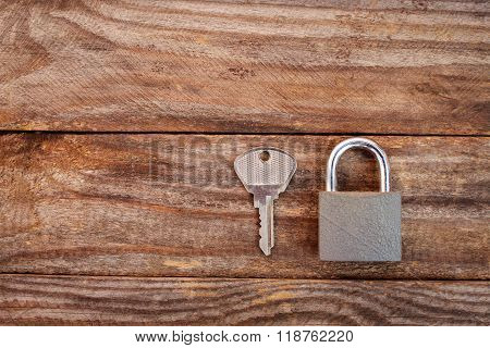 key and lock on wooden background. Toned image.