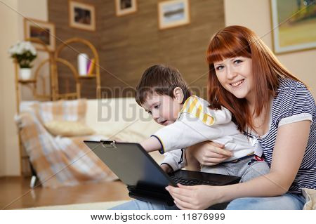 young woman and her son with a laptop at home